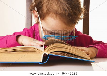 tired of reading little baby girl fell asleep on a book (Knowledge education reading learning concept)