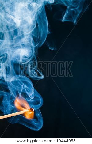Match flame with smoke and black background