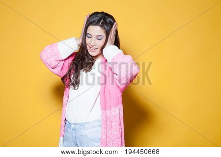 the girl closed her ears hands listens to music