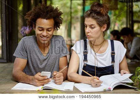 Carefree Afro American Guy Playing Games On His Smart Phone Not Wanting To Study And His Friend Who