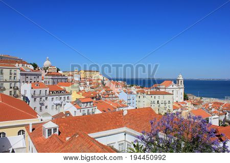 Beautiful panoramic wallpaper of Miradouro Portas do Sol viewpoint in Lisbon, Portugal. Rooftop view of Alfama old town historical district on summer time