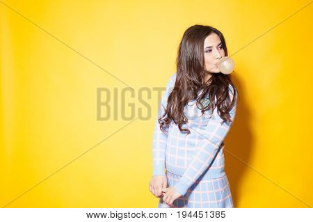 girl with bubble gum against yellow background