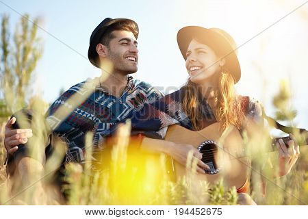 Young Beautiful Female In Black Hat Playing Guitar And Singing Songs To Her Lover Sitting At Greenla