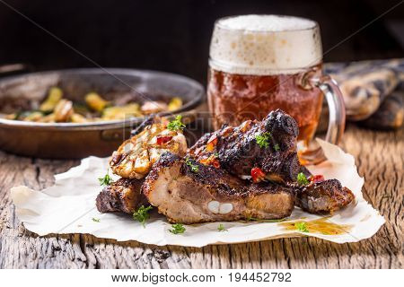 Grill pork ribs Juicy roasted pork ribs with draft beer on rustic oak table.