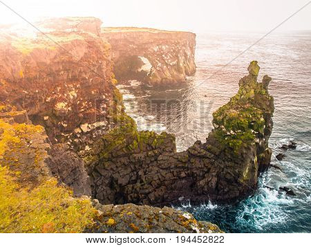 Londrangar, rock lava formation in the sea. Eroded basalt cliffs in the wild sea at coastline on Sneafellsnes peninsula, Iceland.