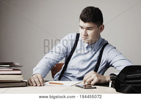 I hate my office work. Young businessman working in office. Low wages overtime working hours lack of career prospects concept. (Body language gestures psychology)