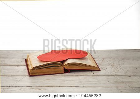 Red heard on a book for background as a symbol of love for literature and knowledge. Vintage styled.