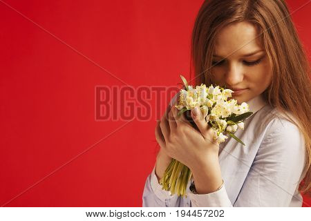 Close-up portrait of Beautiful young blonde girl enjoying nature. Happy Smiling female with gold hair smell a flower with close eyes. (Pleasure nature travel vacation)