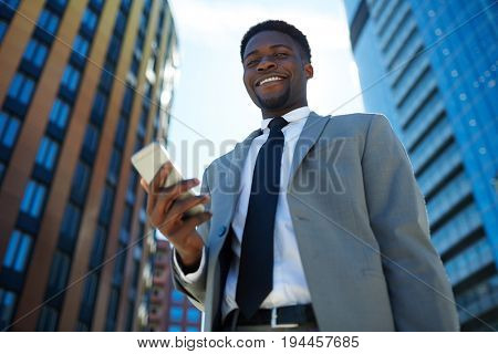 Smiling business leader with smartphone