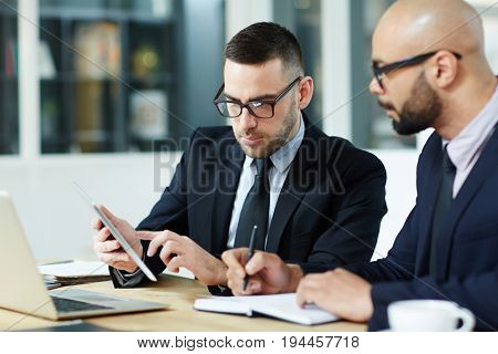Modern analyst making presentation of data to colleague