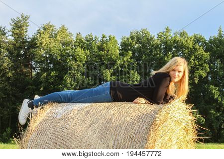 Young Girl Lie Prone On Straw Bale