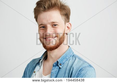 Portrait of young sincere attractive guy smiling looking at camera over white background. Copy space.