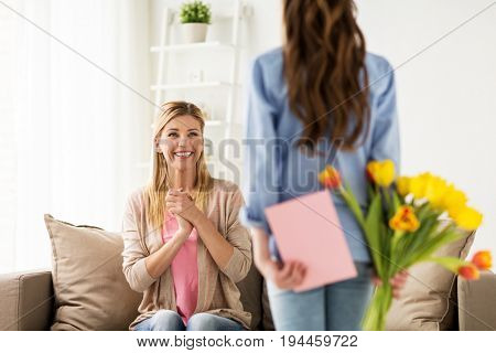 people, family and holidays concept - happy girl giving tulip flowers and greeting card to her mother at home