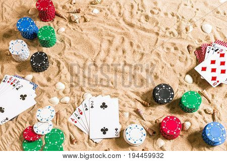 Beachpoker. Chips and cards on the sand with seashells. Top view. Copy space. Flat lay