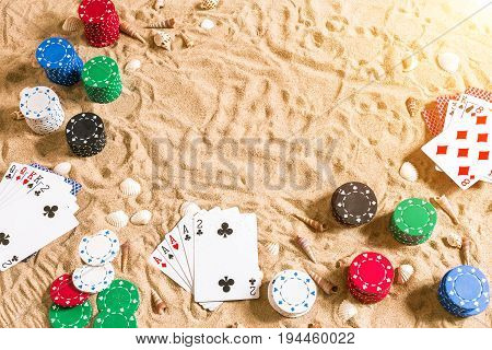 Beachpoker. Chips and cards on the sand with seashells. Top view. Copy space. Flat lay. Beachpoker. Chips and cards on the sand with seashells. Top view