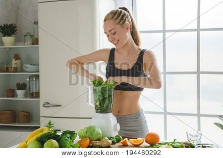 Young female making detox smoothie adding ingredients