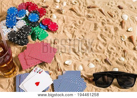 Beachpoker. Chips and cards on the sand. Around the seashells, sunglasses and cold drink in a glass. Top view. Copy space. Flat lay
