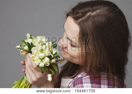 Close-up portrait of Beautiful young girl enjoying nature. Happy Smiling female with gold hair smell a flower with close eyes. (Pleasure nature travel vacation)