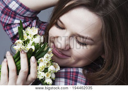 Happy Smiling female with gold hair smell a flower with close eyes. (Pleasure nature travel vacation)