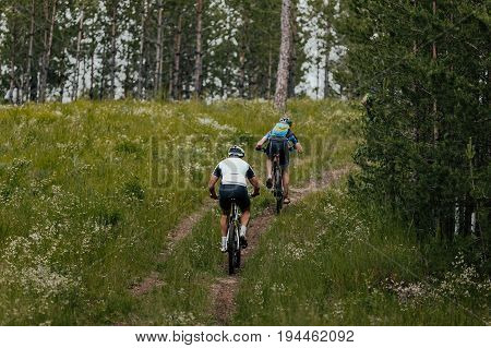 back two man cyclist mountain bike trails
