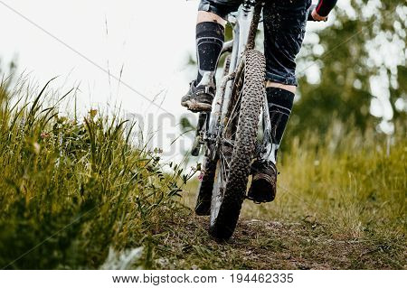 closeup mud mountain bike wheel and legs of cyclist