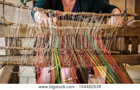 Craftsperson Woman working behind an old wooden loom in workshop