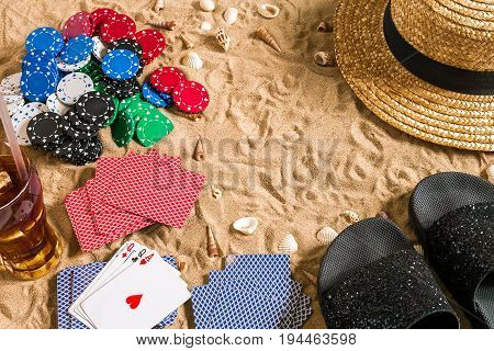 Beachpoker. Chips and cards on the sand. Around the seashells, hat and flip flops. Top view. Copy space. Flat lay