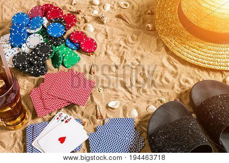 Beachpoker. Chips and cards on the sand. Around the seashells, hat and flip flops. Top view. Copy space. Flat lay. Sun flare