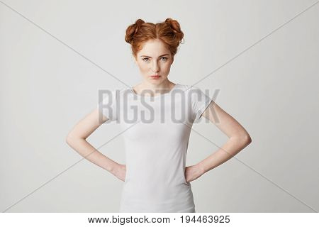 Portrait of young redhead girl looking at camera straight with arms akimbo over white background. Copy space.