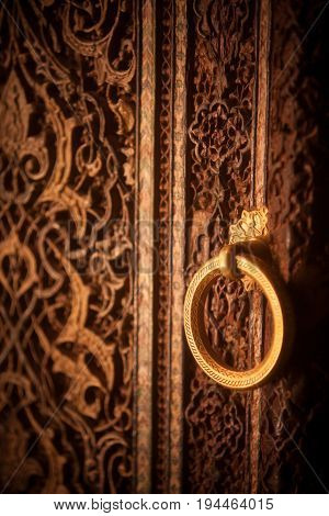 Arabic decorations close up on a wooden door and a round lever ring.