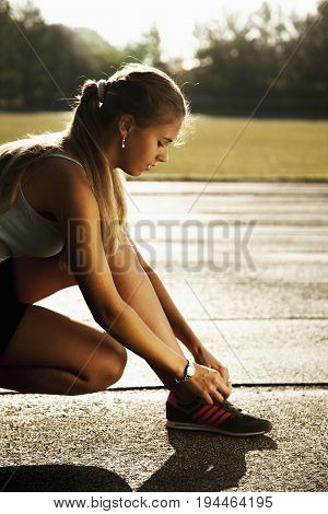 Athletic young brunette girl wearing in sportswear tying her running shoes and getting ready for jogging (Sports healthy lifestyle health willpower concept)