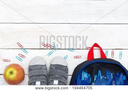 Clip backpack apple and sneakers on a white wooden background