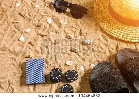 Beachpoker. Chips and cards on the sand. Around the seashells, sunglasses and flip flops. Top view. Copy space. Flat lay. Sun flare
