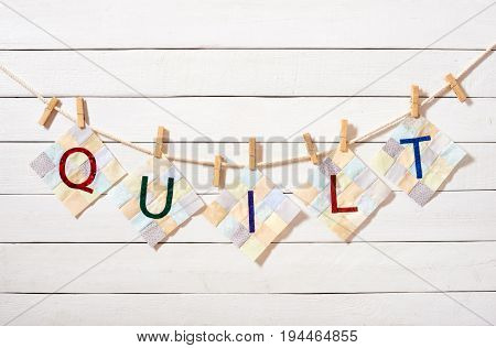 Sewn letters combined as the word quilt attached with clothespins on a rope on a white wooden background