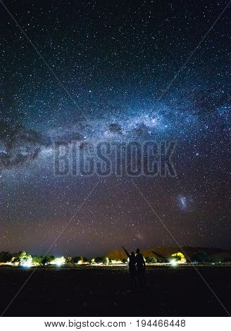 Couple  Pointing To The Galaxy At The Sky.  Milky Way Over Sesriem Camping Site, Namibia.