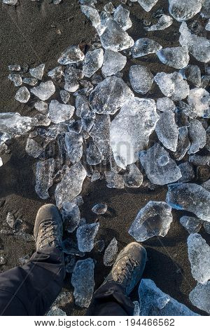 Feets on beach with small icebergs Svalbard