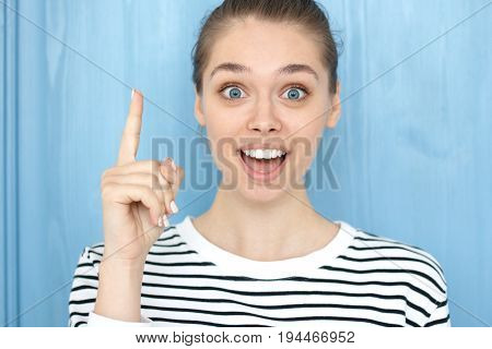 I Have An Idea! Pretty Girl With Hair Bun Keeping Finger Pointed Upwards. Cute Young Caucasian Femal