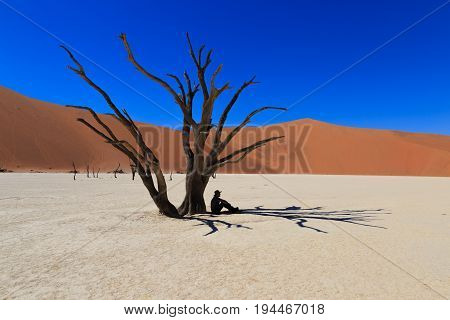 Silhouette of lonely man at Deadvlei, Sossusvlei. Concept of wanderlust in namibian famous desert. Adventure trip travel to african wonders in Namibia