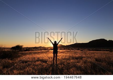 Silhouette Of Woman Open Arms Under The Sunset At African Savanna Landscape.