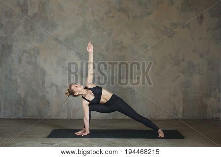 Young Woman Practicing Yoga Pose Bikram Triangle, Trikonasana Against Texturized Wall / Urban Backgr