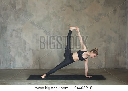 Young Woman Practicing Yoga Side Plank Pose, Vasisthasana Advanced Against Texturized Wall / Urban B