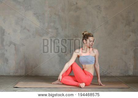 Young Woman Practicing Yoga Sitting Left Twist / Ardha Matsyendrasana Left / Spinal Twist Posture Ag