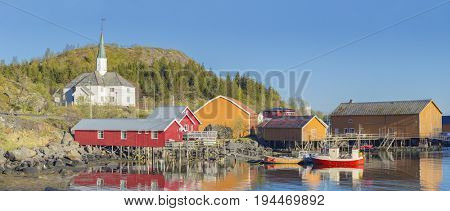 Moskenes on the Lofoten in northern Norway. The Typical Norwegian fishing village of Moskenes under midnight sun, blue sky, with the typical rorbu houses.
