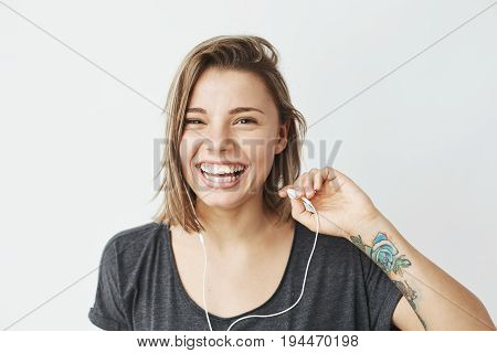 Nice young girl in headphones laughing looking at camera over white background. Copy space.