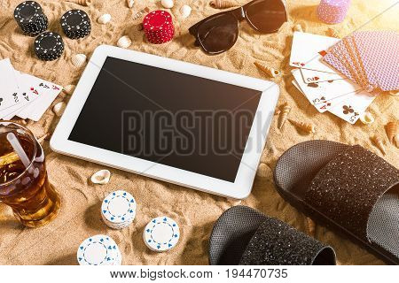 Online poker game on the beach with digital tablet and stacks of chips. Top view. Copy space. Flat lay. Sun flare