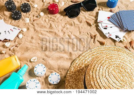 Beachpoker. Chips and cards on the sand. Around the seashells, sunglasses and hat. Top view. Copy space. Flat lay