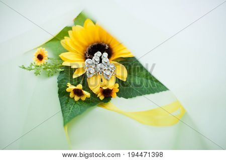 women's wedding earrings from white gold and diamonds closeup on sunflower background. bride's accessories.