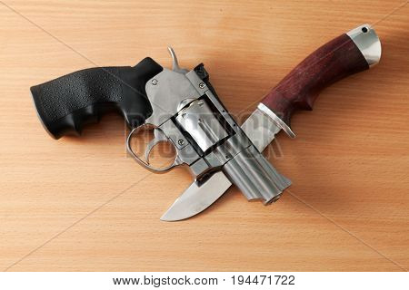 Chromed revolver and a hunting knife on the table