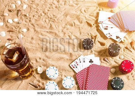 Beachpoker. Chips and cards on the sand. Around the seashells and cold drink in a glass. Top view. Copy space. Flat lay. Sun flare