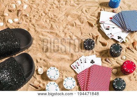 Beachpoker. Chips and cards on the sand. Around the seashells and flip flops. Top view. Copy space. Flat lay